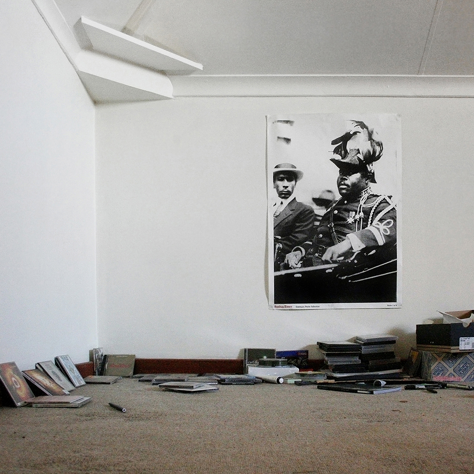 living room with a poster with a famous black leader and dvds and disks spreat out on the floor