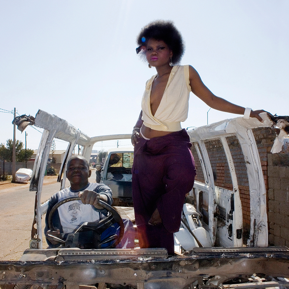 burned out taxi car with prowd driver pretending to drive and a beautyfull fancy black woman with afro standing in a joga pose next to him
