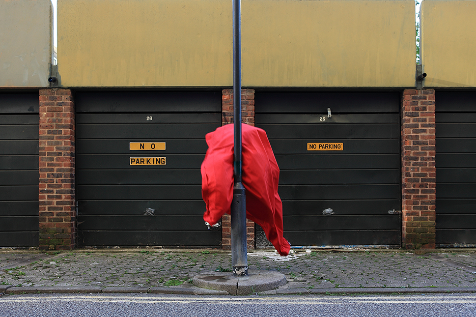 a red flag is flying up a pole in front of a garage complex with the sign no parking in the abandoned Heygate Estate in the London district Elephant and Castle