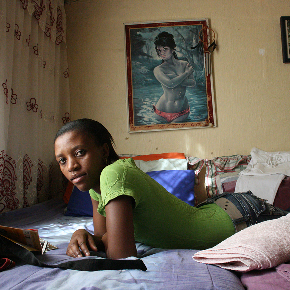 young black woman reading on her bed infront of a mooviepainting of a white naked woman