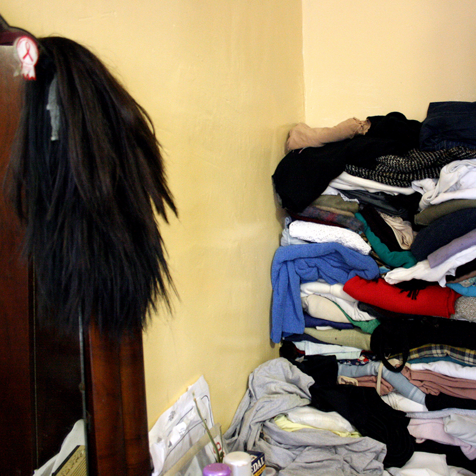 a black wig is hanging over a mirror with an aids sticker on it in the background the clothes are stapled infront of the yellow wall