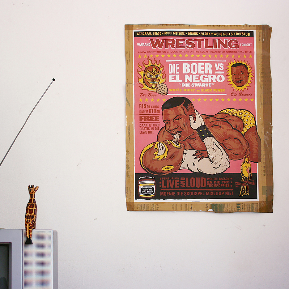 living room with a pink poster of tounge licking wrestlers, one black one white and the headline: die boer vs el negro, in the left corner a little wooden and painted giraffe is sitting on a silver tv