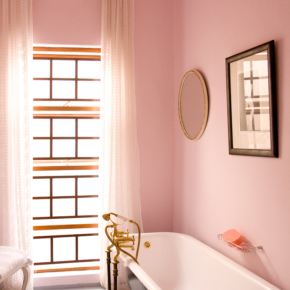 a pink painted bathroom with golden handleswindow frames and mirrors