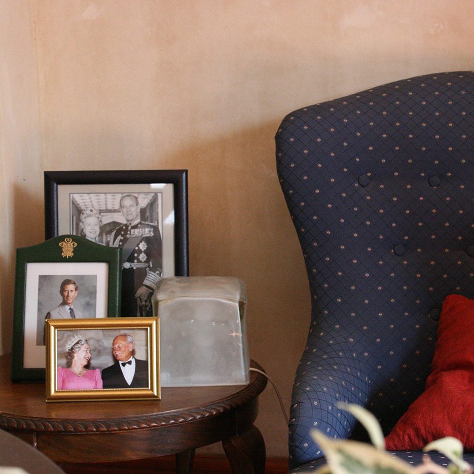 living room with a blue ears armchairqueen chair with a red pillow, on the little table next to it are portraits of the royal british family