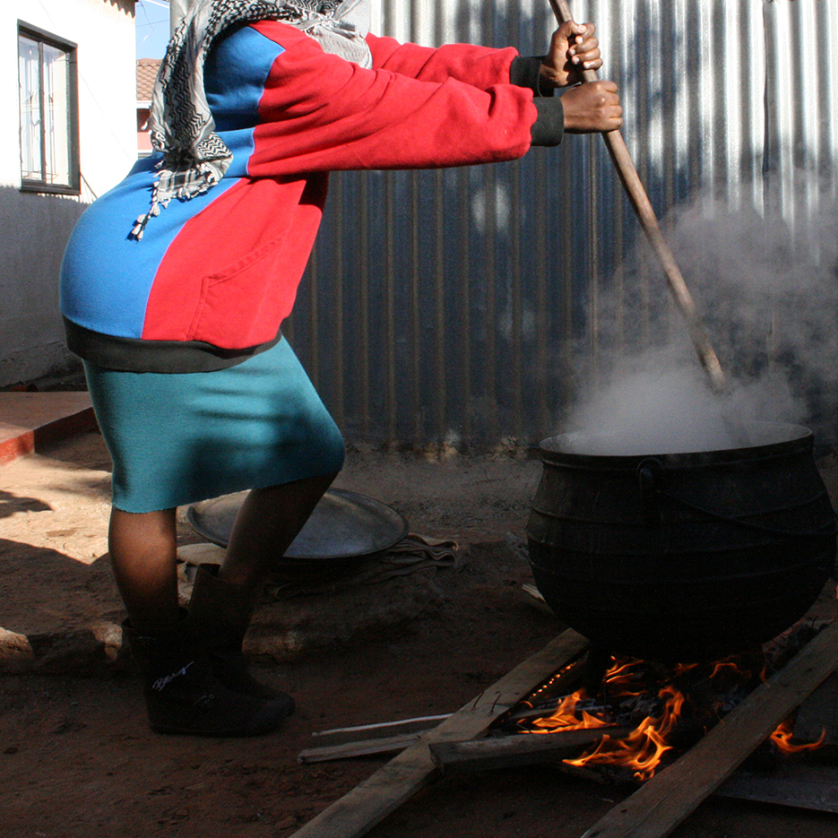 young woman in fancy clothes stiring in a giant smoking pot outdoors in the township kagiso