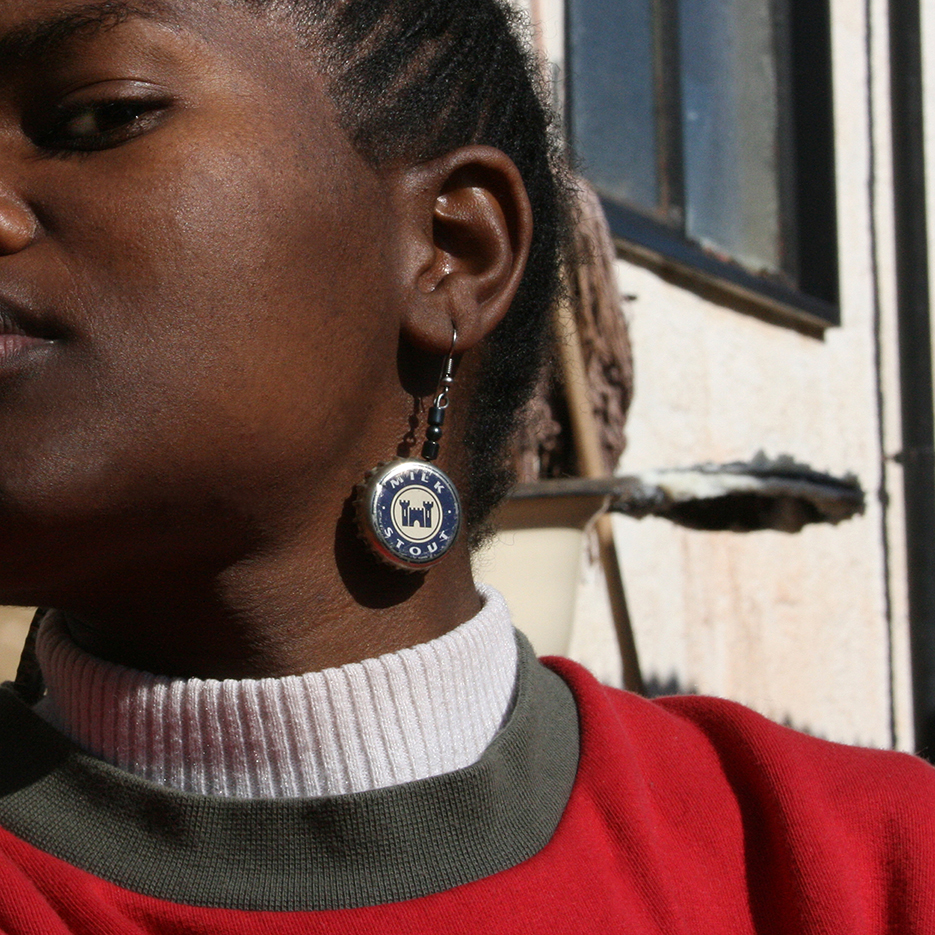 township kagiso: portrait of a joung woman with a earring made from a beer cup saying milk stout