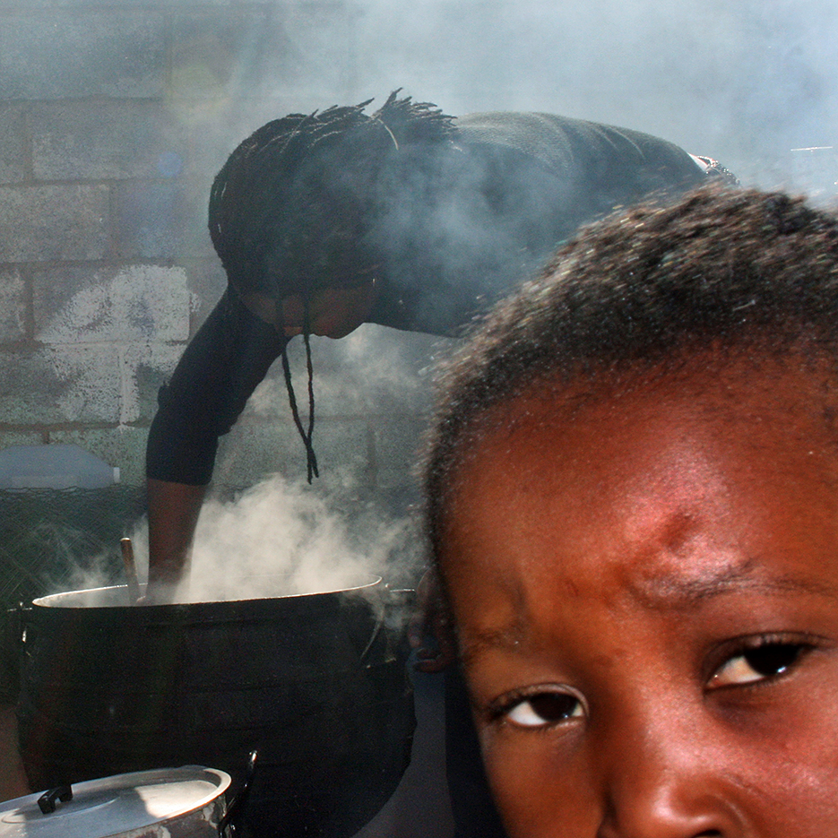 black woman with dread locks stiring in a smoking pot outdoors, a small girl in the very front is eying critically into the camera