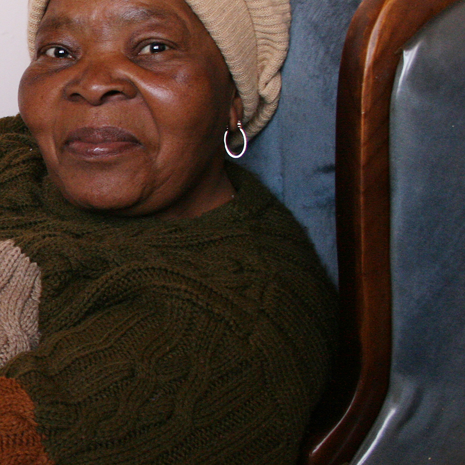 older lady smiling mildly into the camera in the township kagiso