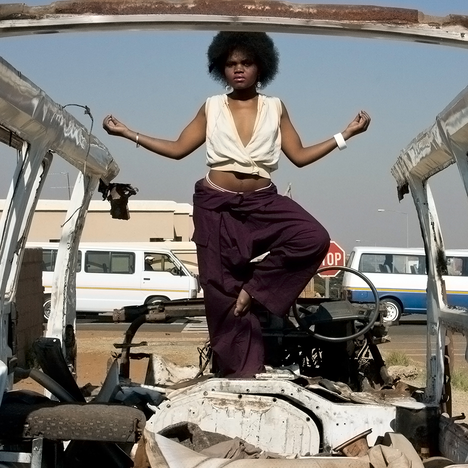 burned out taxi car with  a beautyfull fancy black woman with afro standing in a joga pose