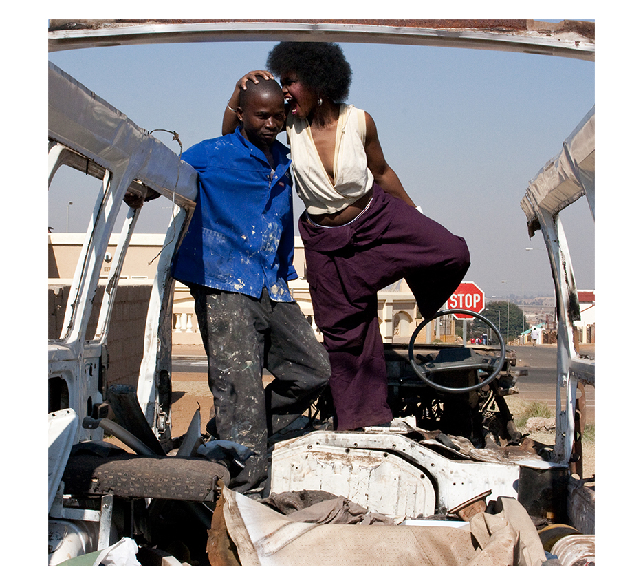 burned out taxi car with prowd owner  and a beautyfull fancy black woman with afro hugging his head pretending to bite him