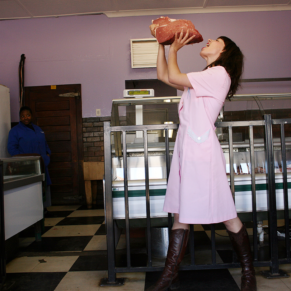white girl in a pink maidens dress holding a big peace of meat above her head predending to bite in it, the black bucher woman in the back is watching this unbelievingly