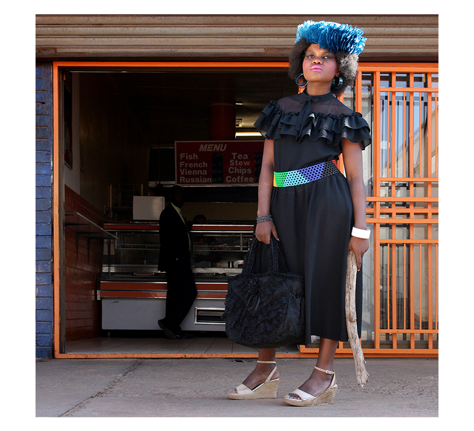 black girl in a fancy black dress and a blue feather hat is standing with big wooden stick infront of a bucher looking critically into the camera