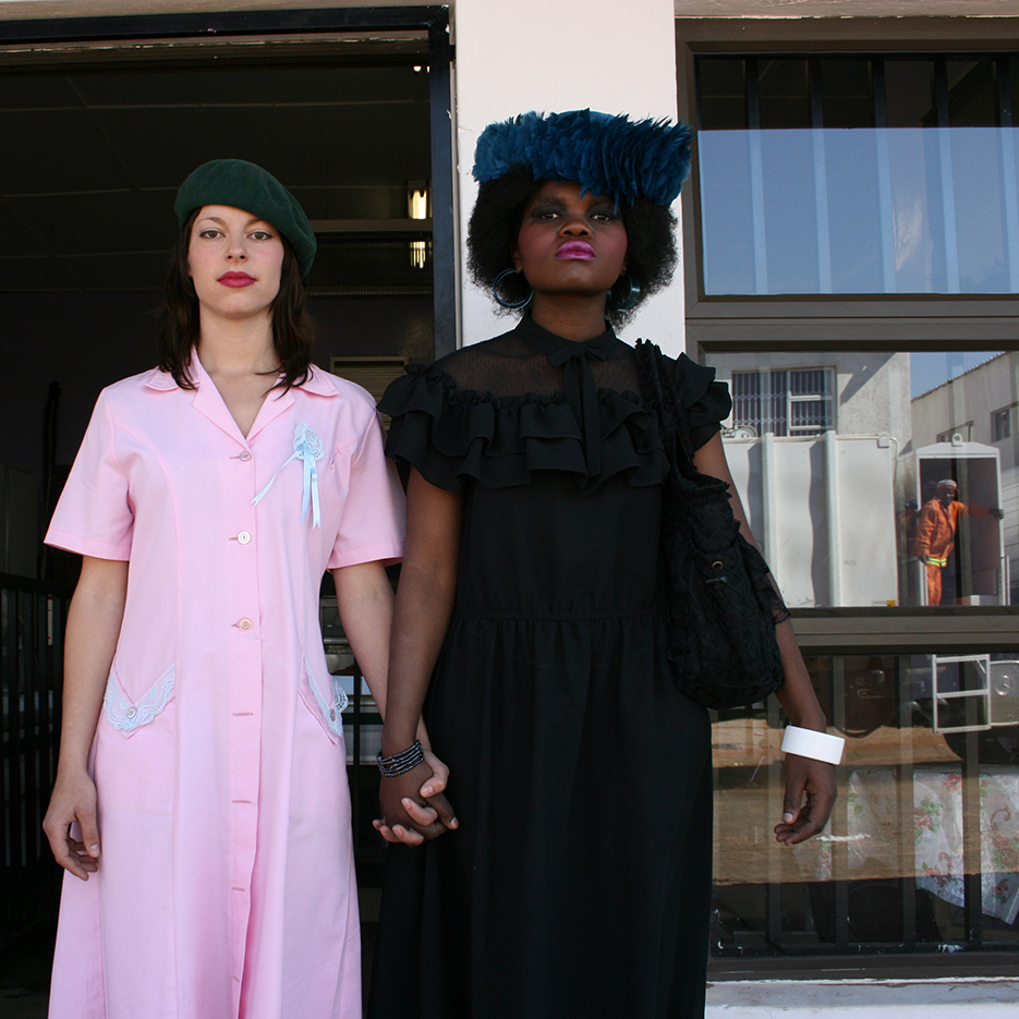 white girl in a pink maidens dress and black girl in fancy black dress with a blue feather hat holding hands infront of a window that mirrors a garbagecar with an orange dresses garbage collector looking at them