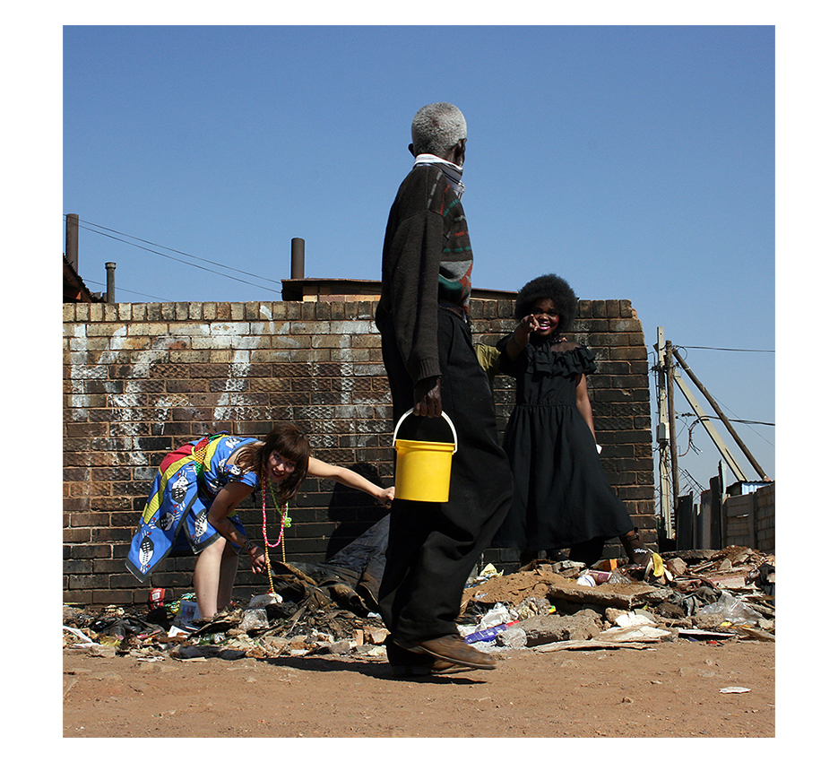 old blaack man in dark close is carrying a small yellow bucket accroos a white and a black girl surching a garbage pile, pointing and loughing at him