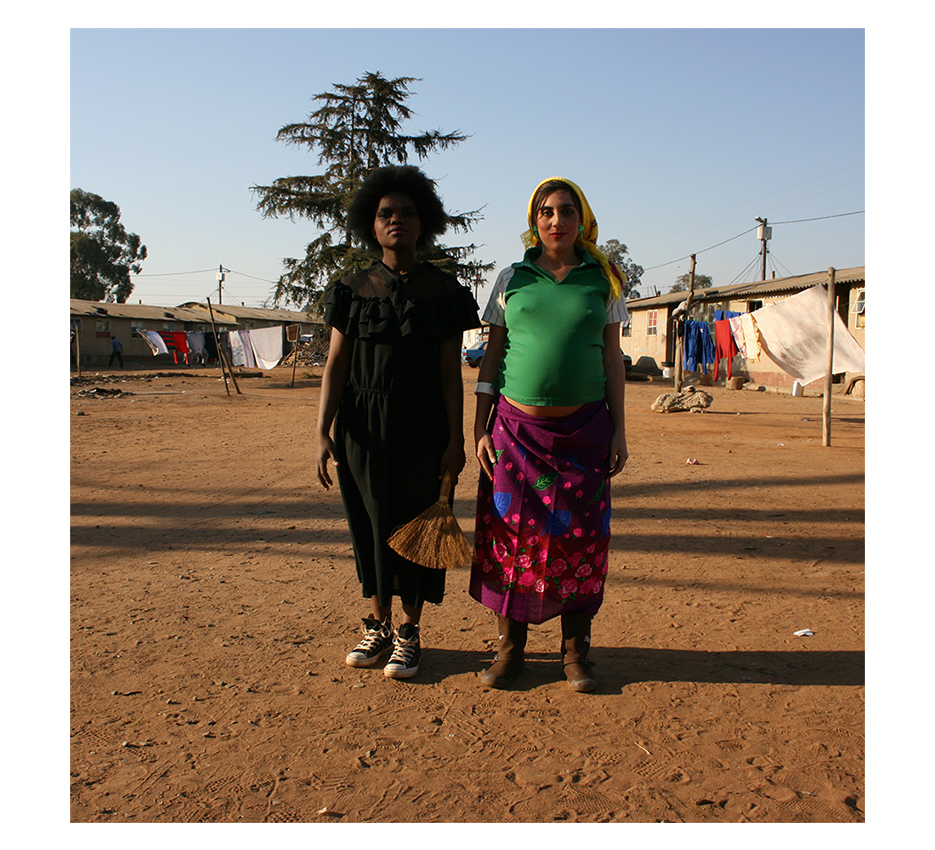 a balck girl in a black dress and a small broom standing shoulder to shoulder with a pregnant white girl together facing the camera in a poor house complex with drying close