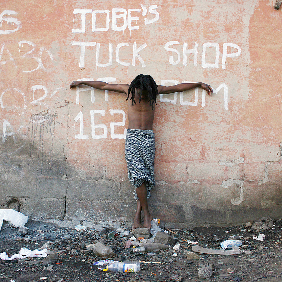 black jesus with palestinian cloth around his hip, standing in garbage in front of a written on wall, saying: Jobes' Tuck Shop