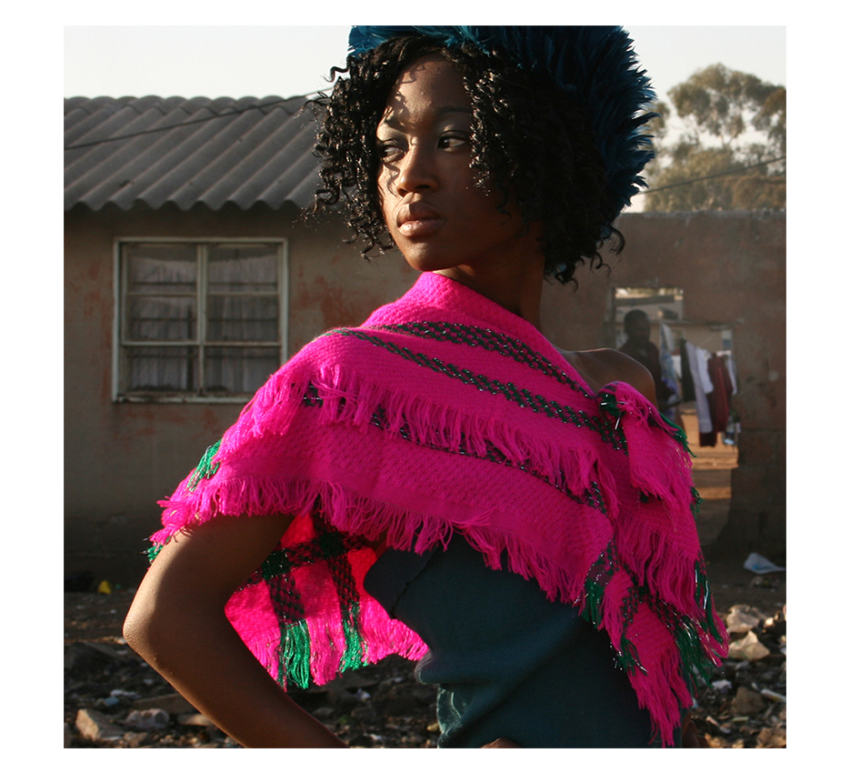 beautyfull black girl with a pink woolen scarf posing infront of a torn down house