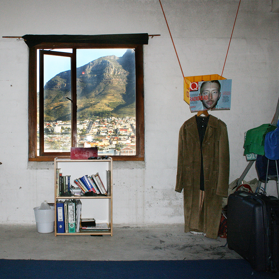 living room with a window viewing the table mountain, an empty beer box is hanging from the sealing decoratet with a radiohead singers portrait, a mantel hanging from it is using the box as a wardrobe