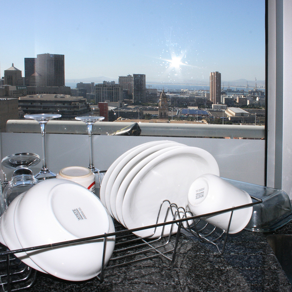 drying dishes on a kitchensink of a scyscraper, behind the dishes is a large window with a great view over the Cape Town skyline
