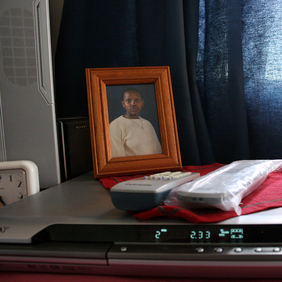 framed portrait of a black young woman on a dvd player with plastic wrapped remote control