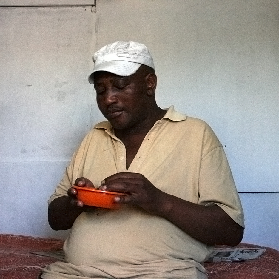 black man with white cap is eating chicken out of a orange plastic boul with his fingers