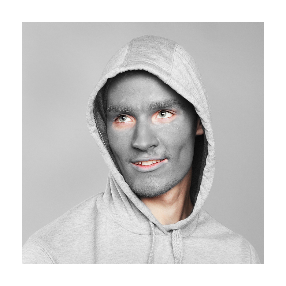white young man with  grey facepaint in a grey hoody sits in front of a grey background looking to the up left, with a lite smile