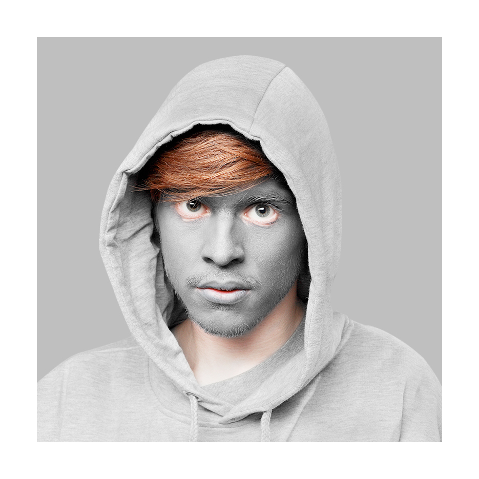 white young man with red hair and grey facepaint in a grey hoody sits in front of a grey background looking into the lens , with an innocent smile