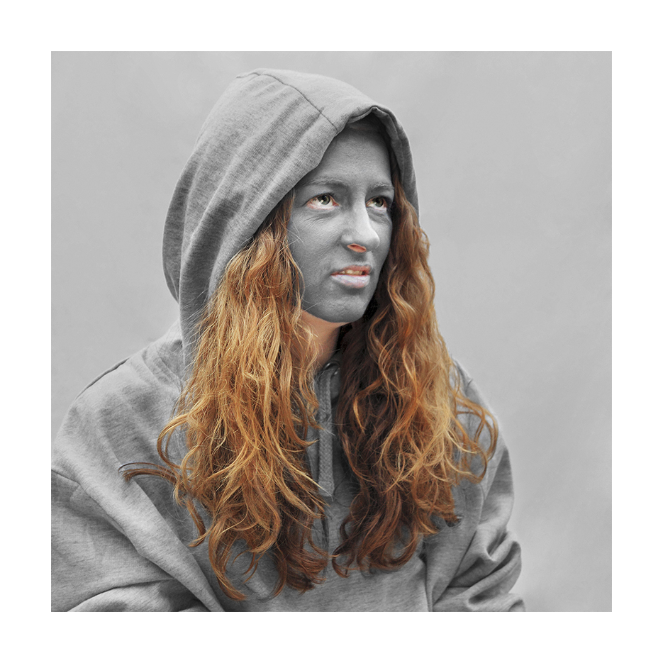 white girl with red hair,  grey facepaint in a grey hoody sits in front of a grey background looking anoyed